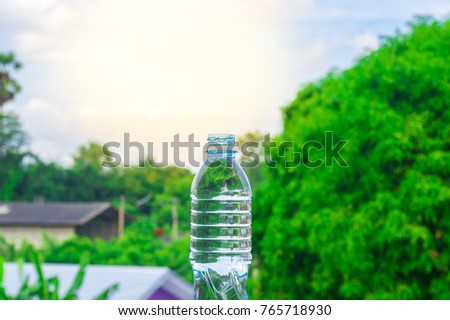 Bottle water made to plastic on sky and tree blurry background.Using wallpaper for package or product, refreshing image and copy space.
