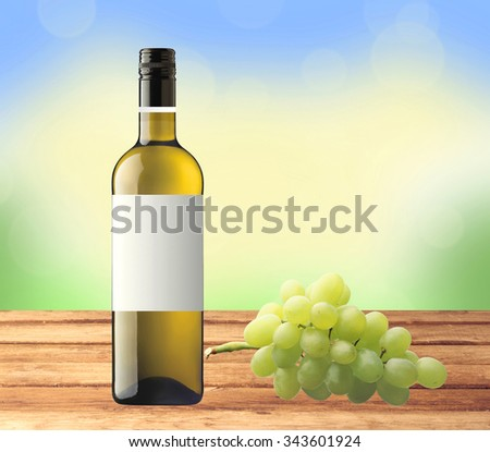 bottle white wine and green grape on wooden table over nature background - stock photo