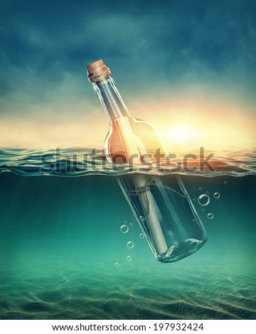 Bottle with a message in water - stock photo