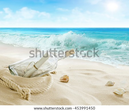 Bottle with a message on the beach. - stock photo