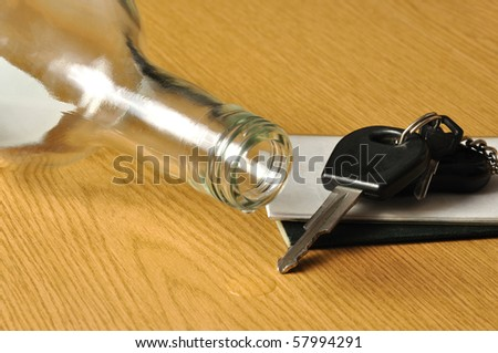 Bottle with alcohol and car keys on a table