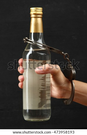 Bottle with alcohol drink in hand on a dark background. The concept of alcoholism