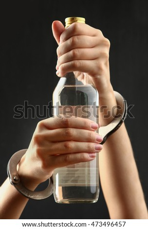 Bottle with alcohol  in hands on a dark background. The concept of alcoholism