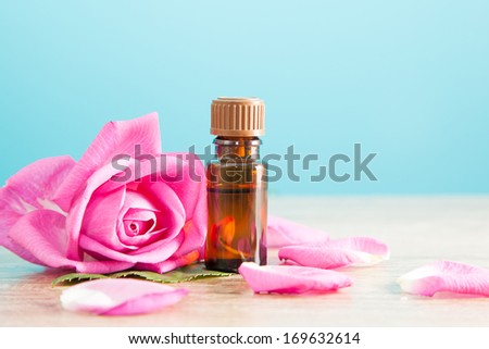Bottle with aromatic oil and pink rose on wooden table - stock photo