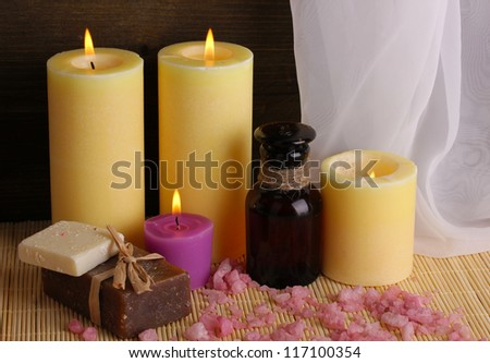 Bottle with aromatic oils with accessories for relaxation close-up on wooden table on wooden background
