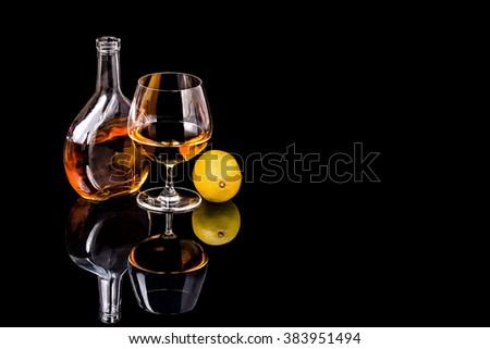 Bottle with Goblet of Brandy and lemon on the mirror black surface - stock photo