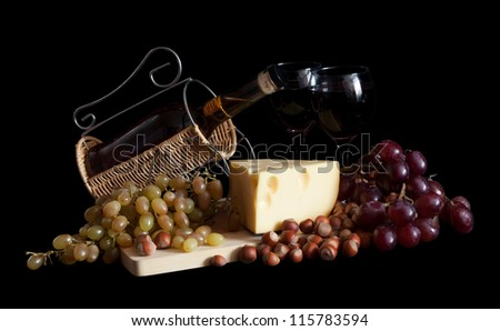 bottle with  grapes and cheese over black background - stock photo