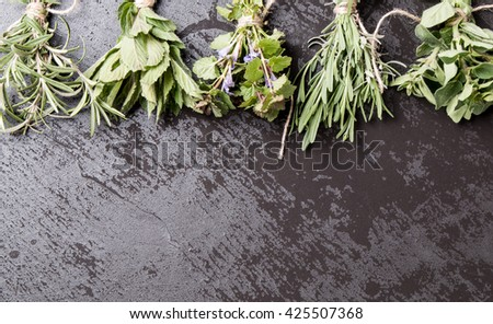 Bottle with herbs on black stone background. Mint, thyme, balm and other medicinal herbs - stock photo