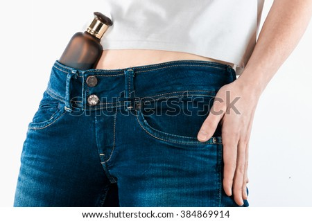 Bottle with perfume liquid behind a belt of women's jeans . The concept of female alcoholism .