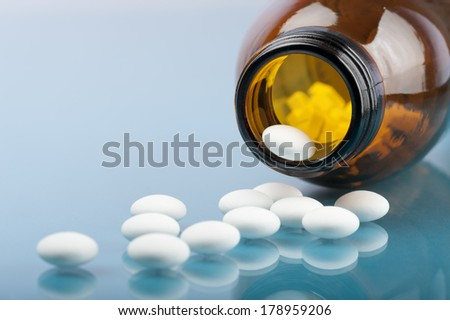 bottle with pills and tablets on blue background