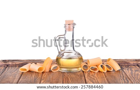 Bottle with yellow olive oil, sunflower oil and spaghetti noodles pasta isolated on a table, isolated on white background