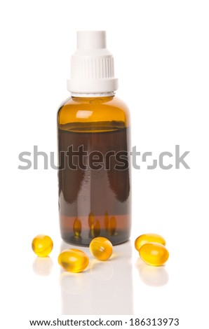 Bottle with yellow pills around isolated on white