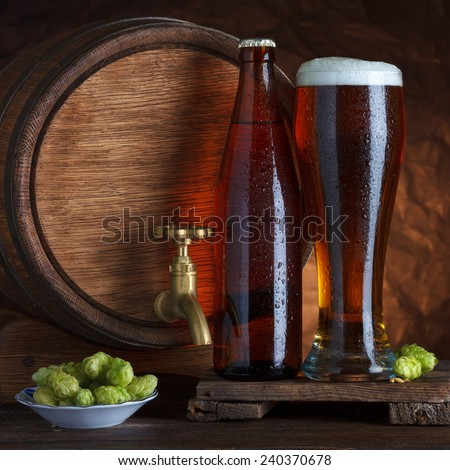 Bottled and unbottled beer glass with vintage old barrel and fresh hops for brewing still-life - stock photo
