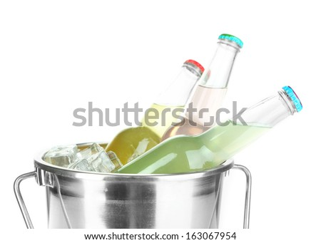 Bottled drinks in ice bucket isolated on white - stock photo