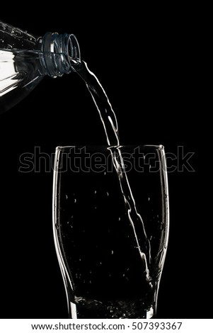 Bottled water poured into glass of water. silhouette, backlit, isolated on black background.