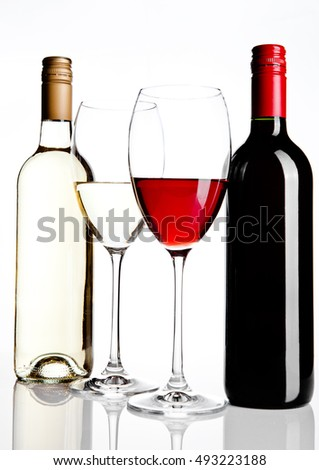 Bottles and glass of red and white wine reflection on white background