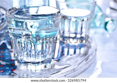 Bottles and glasses of clear liquid on a wet table