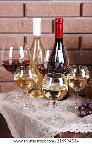 Bottles and glasses of wine and ripe grapes on table on brick wall background - stock photo