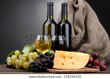 bottles and glasses of wine, cheese and grapes on grey background
