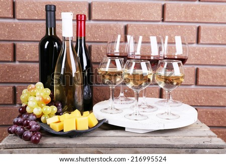 Bottles and glasses of wine, cheese and ripe grapes on box on brick wall background - stock photo
