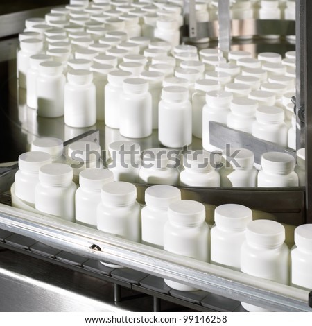 Bottles coming out of the pill counter in a pharmaceutical processing facility. - stock photo