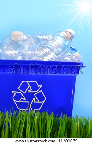 Bottles in recycling container bin in the grass - stock photo