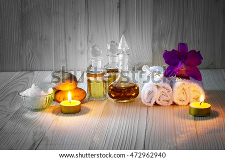 Bottles of aromatic oils with candles, pink orchid, stones and white towel on vintage wooden background with vignette,spa treatment concept