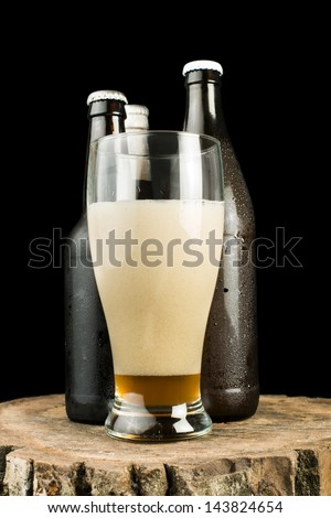 Bottles of beer and beer mug on stump. White isolated studio shot.