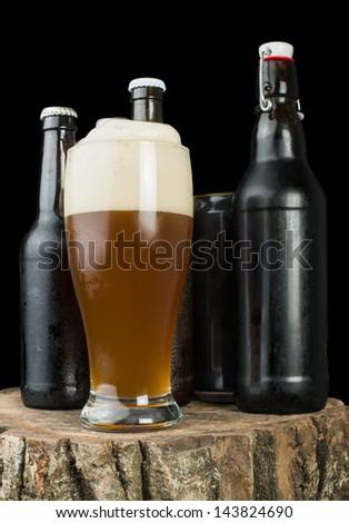 Bottles of beer and beer mug on stump. White isolated studio shot. - stock photo
