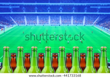 bottles of beer before tv showing soccer - stock photo