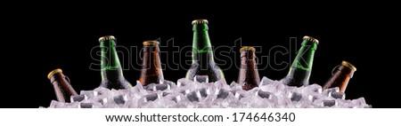 bottles of beer on ice on black background - stock photo