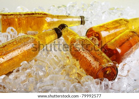 Bottles of cold beer lying in the ice. Close view. - stock photo
