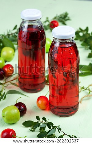 Bottles of compote with summer berries