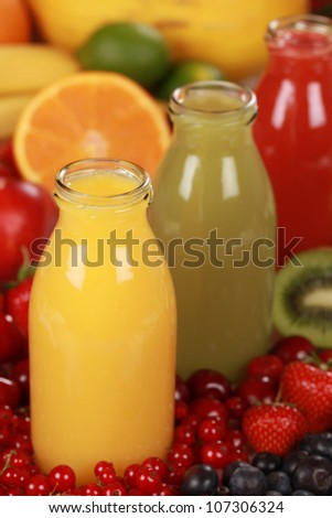 Bottles of different kinds of smoothies surrounded by fresh fruits - stock photo