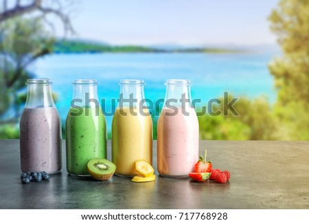 Bottles of different protein shakes and landscape on background