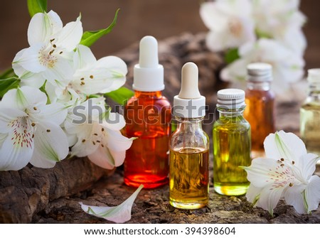 Bottles of essential aromatic oils and fresh flowers