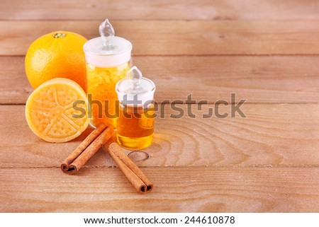 Bottles of essential oil and bath salt with orange, bar of soap and cinnamon on wooden background - stock photo