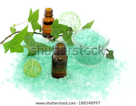 Bottles of essential oil, bath salt and branch of ivy isolated on white background
