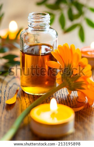 bottles of essential oil,candles and flowers - stock photo
