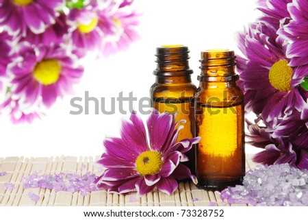 Bottles of Essential Oil with Flowers and Salt - stock photo