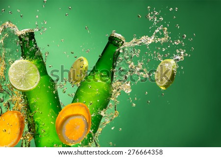 Bottles of fruit beer with splash around on green background. - stock photo