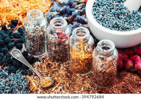 Bottles of healing herbs and mortar with lavender flowers, herbal medicine. Retro styled. - stock photo