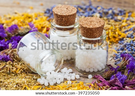 Bottles of homeopathy globules and dry healthy herbs on table. Selective focus. - stock photo