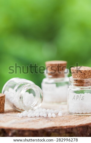 Bottles of homeopathy globules on green background - stock photo