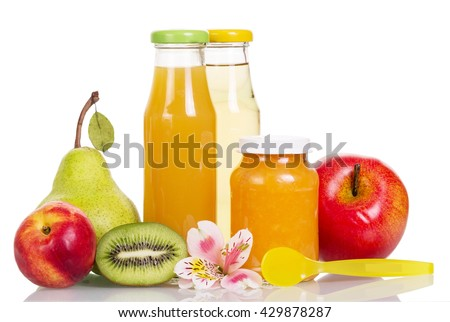 Bottles of juice and jar of pureed fruit, spoon, orchid flower isolated on white background.
