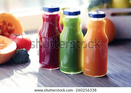 Bottles of juice with fruits and vegetables  on windowsill close up - stock photo