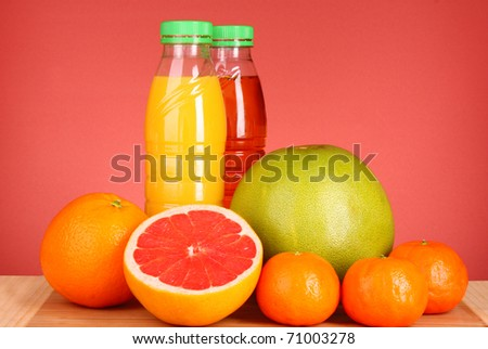 bottles of juice  with ripe fruits on yellow background