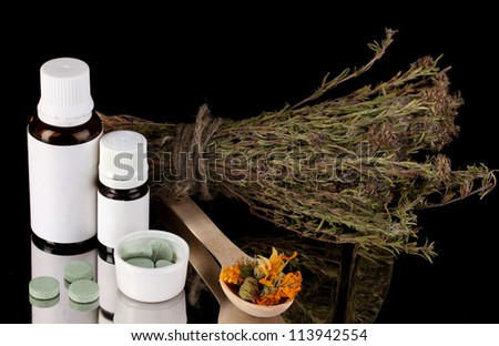 bottles of medicines and herbs on black background. concept of homeopathy - stock photo