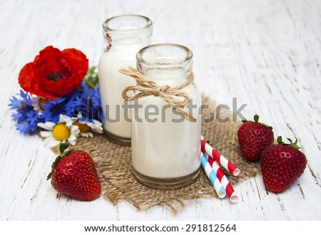 Bottles of milk with strawberry and wildflowers on a old wooden background - stock photo