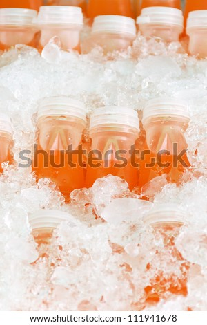 bottles of natural orange juice in the middle of ice - stock photo